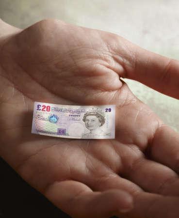 appendage: Mans hand holding tiny British Pound