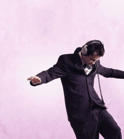 bambino: Studio shot of businessman wearing headphones and dancing