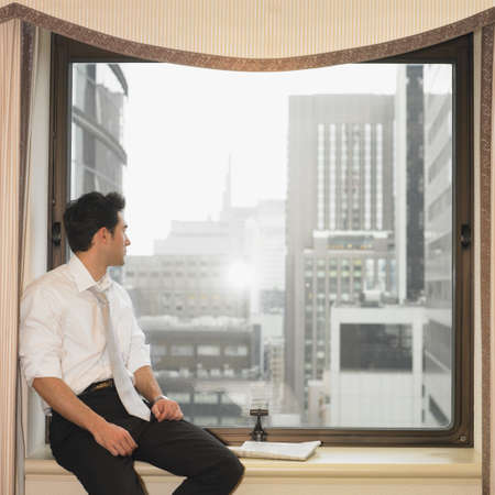 go inside: Businessman sitting in window and looking out