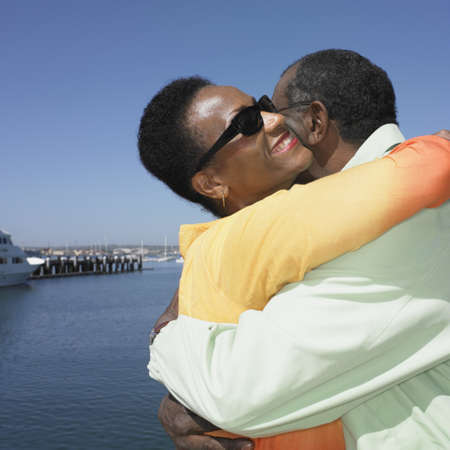 solicitous: Senior African couple hugging next to water LANG_EVOIMAGES