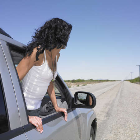 adventuresome: Woman leaning out of car window on deserted road