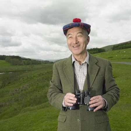 searcher: Senior Asian man with binoculars in countryside