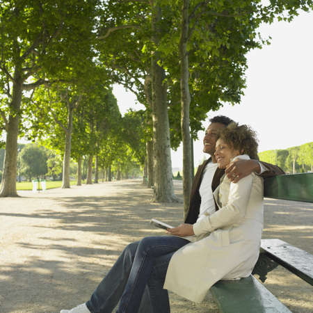 finding a mate: African couple sitting on park bench smiling