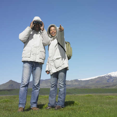 adventuresome: Couple using binoculars and wearing winter jackets with snow-capped mountains in background