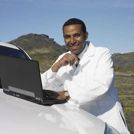 unconcerned: Man in lab coat using laptop on car hood in deserted rural area