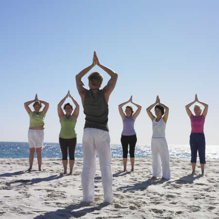 wooing: Group of women practicing yoga with instructor on beach