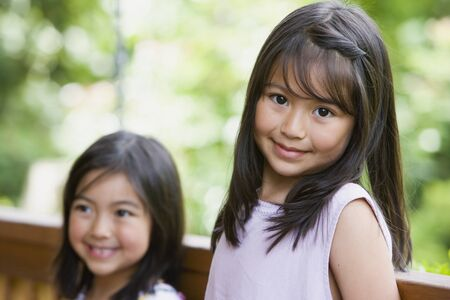 Young Asian sisters smiling outdoors Stock Photo