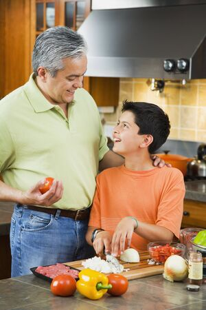 kinfolk: Hispanic father and son chopping vegetables in kitchen