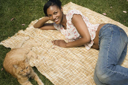 fathering: African woman laying on blanket in grass with cat