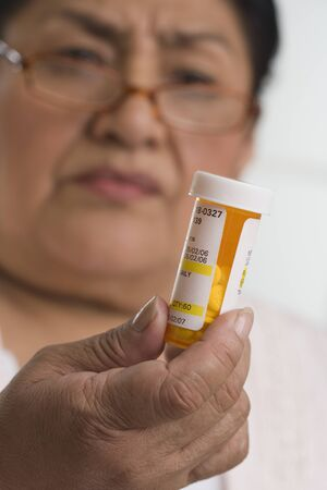 relishing: Senior Hispanic woman looking at medication bottle LANG_EVOIMAGES