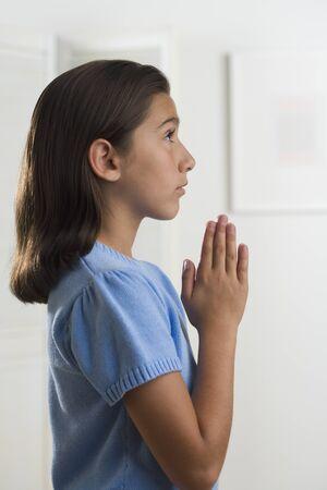 indoors: Hispanic girl praying indoors LANG_EVOIMAGES