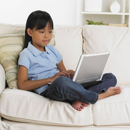 seriousness skill: Young Asian girl using laptop of sofa LANG_EVOIMAGES
