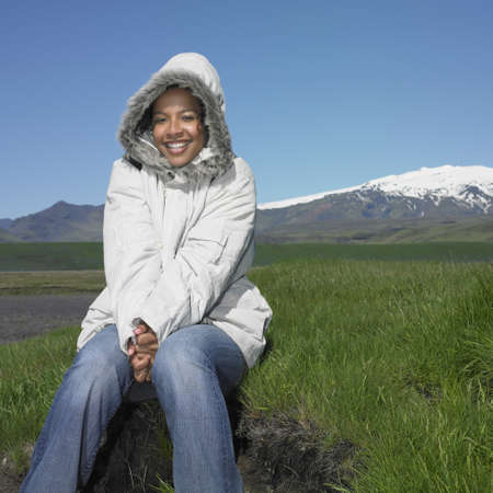 finding a mate: African woman wearing winter jacket and smiling outdoors