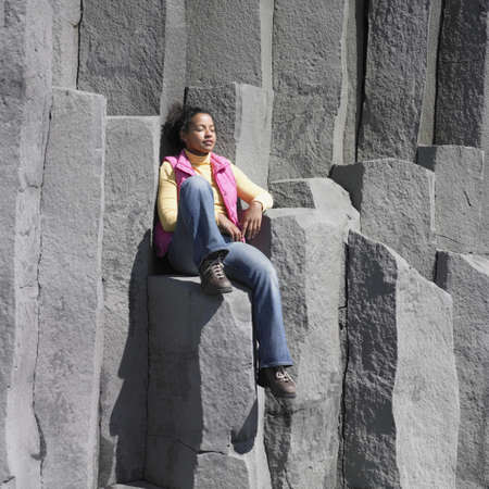 mischievious: Woman sitting on rock ledge with eyes closed