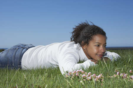 adventuresome: African woman laying in grass smiling