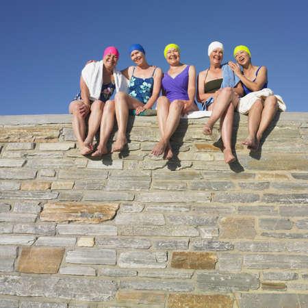 Gruppe ältere Frauen in Badeanzügen sitzen auf Steinmauer LANG_EVOIMAGES