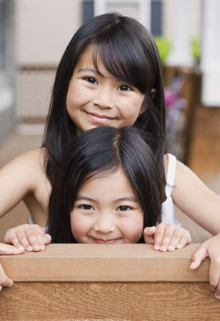treading: Young Asian sisters hugging and smiling indoors