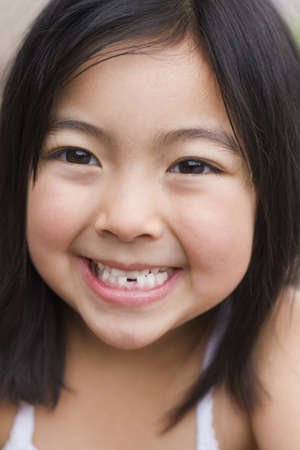 Close up of young Asian girl smiling with tooth missing