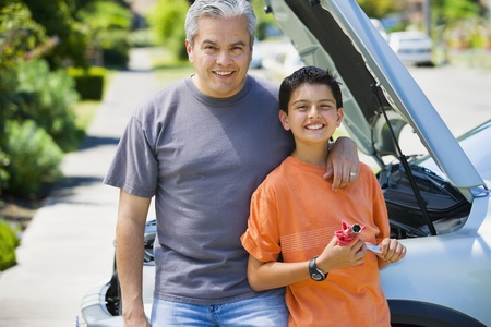 Hispanic father and son standing in front of car with hood up 스톡 콘텐츠