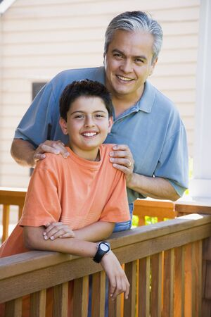poppa: Hispanic father and son smiling on porch