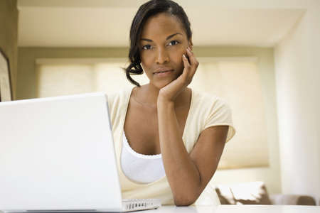 casualness: African woman using laptop indoors