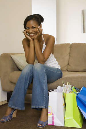 casualness: African woman smiling on sofa next to shopping bags LANG_EVOIMAGES