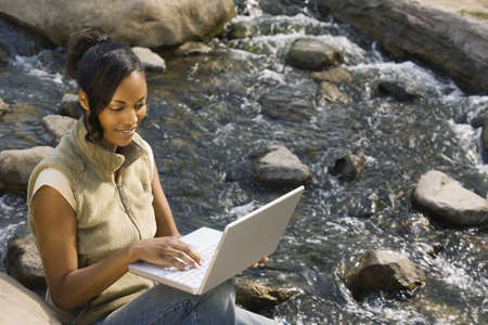 davenport: African woman sitting next to flowing water using laptop LANG_EVOIMAGES