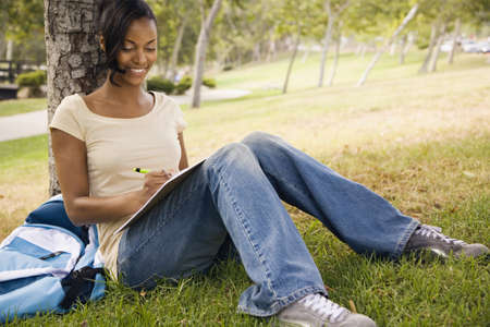 casualness: Young African woman with backpack leaning on tree and writing