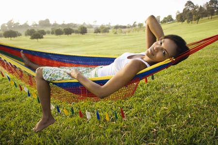 hammock: African woman laying in hammock smiling LANG_EVOIMAGES