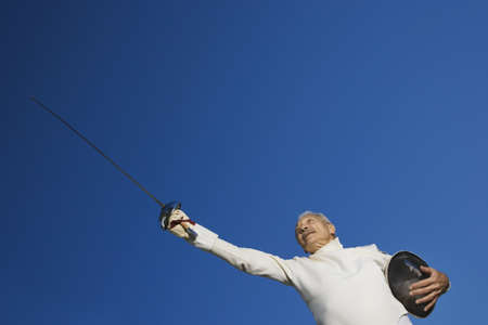 dressup: Low angle view of senior male fencer pointing epee