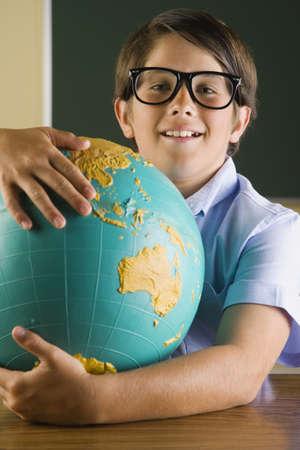 schoolroom: Hispanic boy holding globe in classroom LANG_EVOIMAGES