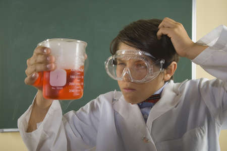 endangering: Boy wearing lab coat and goggles and holding beaker in classroom