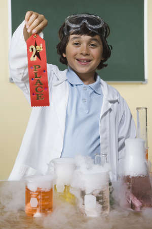 jeopardizing: Young boy with science project holding second place ribbon LANG_EVOIMAGES
