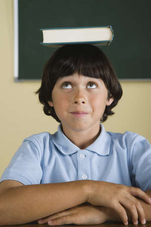 endangering: Boy with book on head in classroom