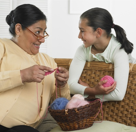 Hispanic grandmother and granddaughter with knitting supplies Banco de Imagens