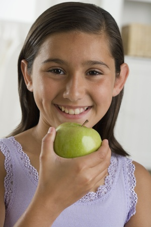 Hispanic girl smiling with apple indoors