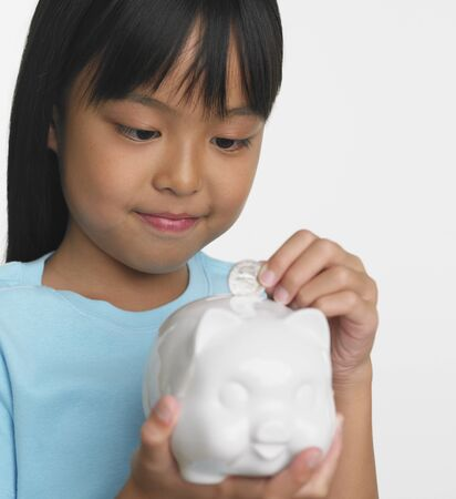 casualness: Young Asian girl putting coin in piggybank