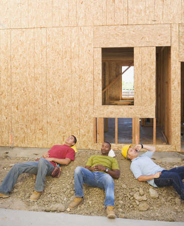 Male construction workers relaxing at construction site Stock Photo