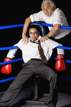 Bruised businessman sitting in corner of boxing ring with coach Stock Photo