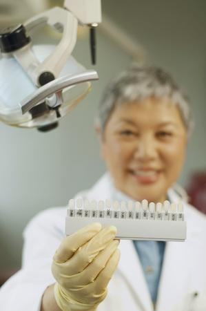 relishing: Senior Asian female dentist holding tooth color samples LANG_EVOIMAGES