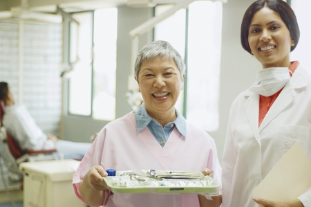 Indian female dentist and senior Asian female dental assistant smiling