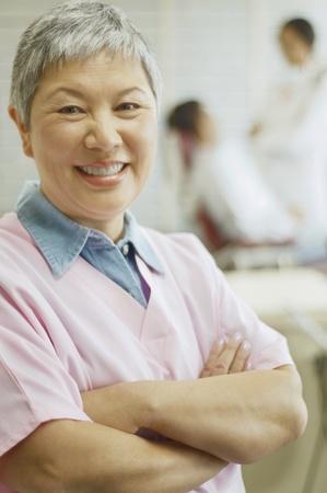 giver: Senior Asian female dental assistant smiling
