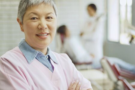bestowing: Senior Asian female dental assistant with dentist and patient in background