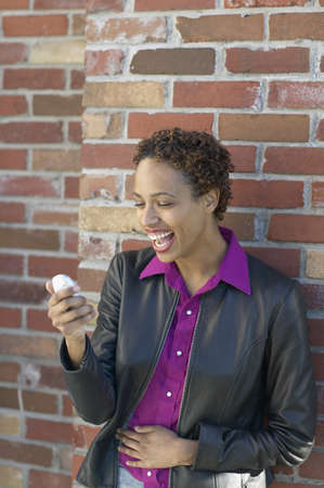 jamaican ethnicity: African woman laughing and using cell phone LANG_EVOIMAGES