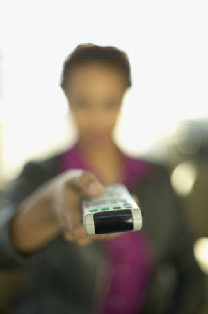 jamaican ethnicity: Woman pointing remote control
