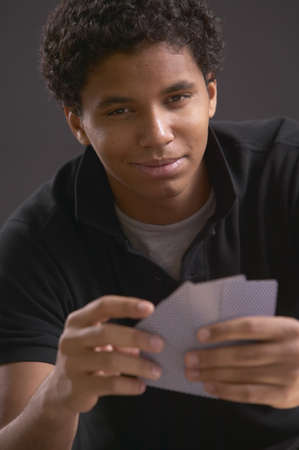 casualness: Young African man holding playing cards