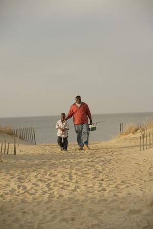 アフリカの父と息子の漁具とビーチの上を歩いて