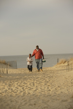 African father and son walking on beach with fishing gear