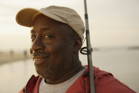 fishing pole: Close up of African man holding fishing pole