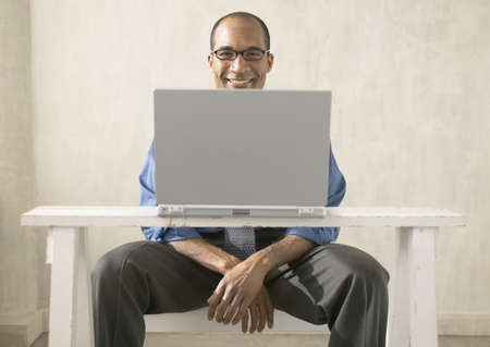 facing away: African businessman sitting behind laptop LANG_EVOIMAGES